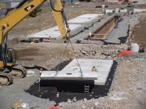 Swinging precast concrete roof panels into place on site for a stormwater retention system.