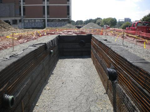 Inlet pipes from storm drains and roof liters empty into stormwater detention vault and infiltrates into porous open graded stone.