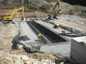 Excavators feed stone for retaining wall construction on storm water project.