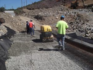 Mechanical compaction of stone on stormater retention project.